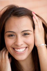 young hispanic woman smiling with her hand in her hair