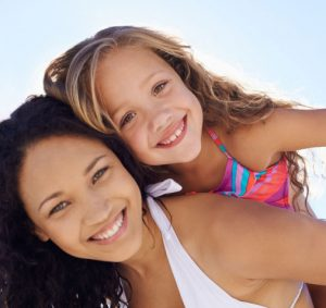 young woman and little girl smiling