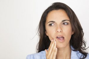 young woman feeling sensitivity in her tooth and holding her cheek