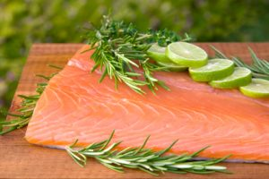 filet of salmon garnished with rosemary and lime