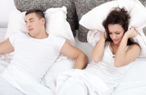 young woman struggling to sleep as her young male partner snores