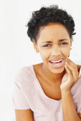 young woman holding her cheek in pain from a toothache